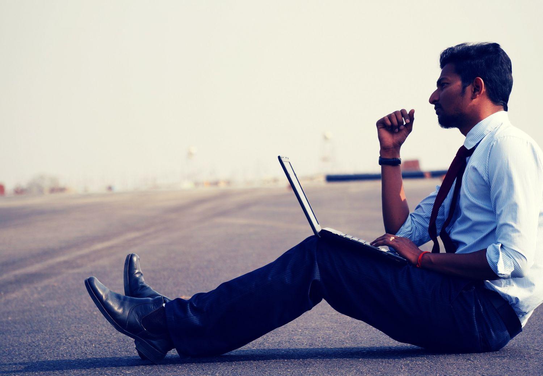 Ein Mann sitzt mit seinem Laptop auf einem asphaltierten Feld