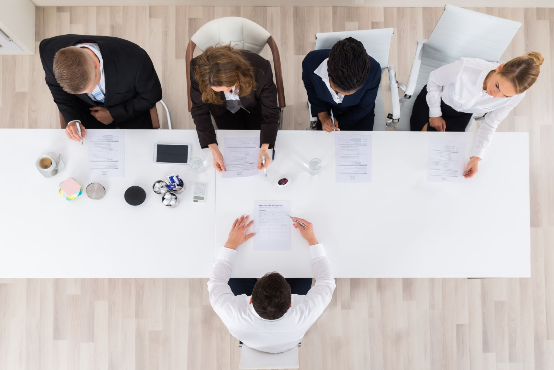Mitarbeiter sitzen an einem Tisch, von oben gesehen
