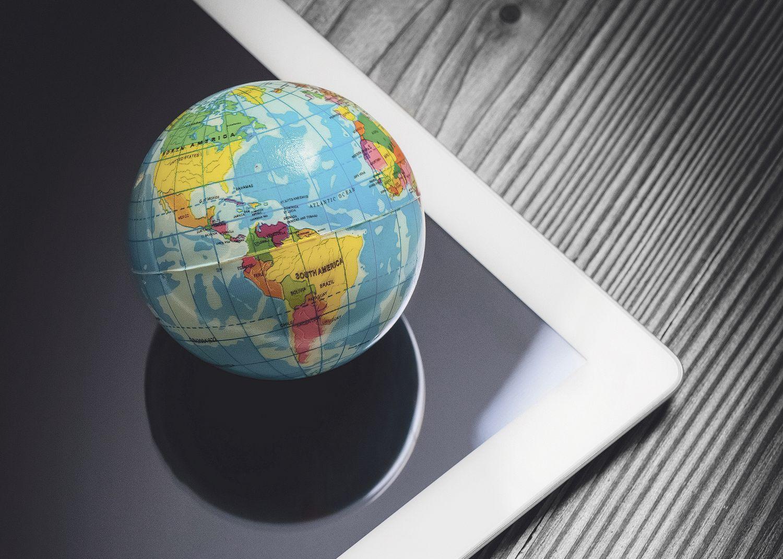 Plastikmodell der Erde auf einem Tabletbildschirm