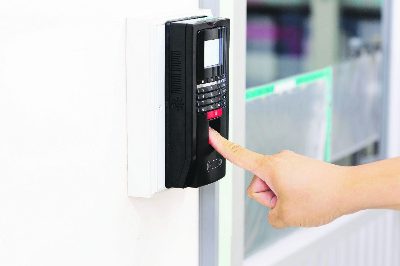 Jemand identifiziert per Fingerabdruckerkennung an einer Tür