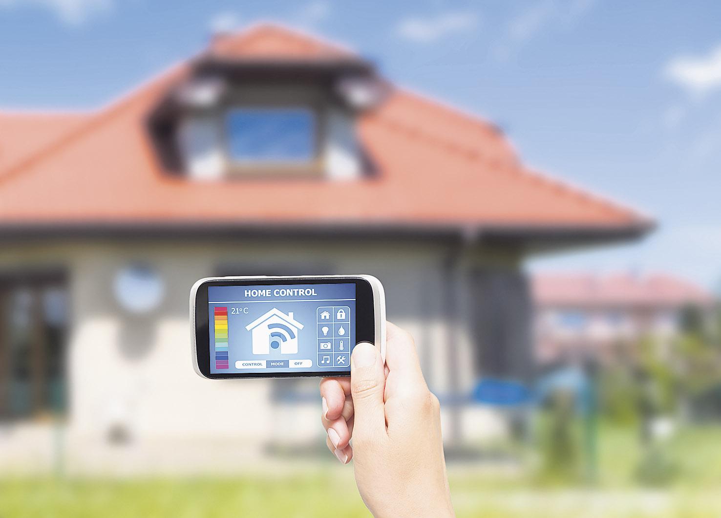 Jemand hält ein Smartphone vor ein Wohnhaus
