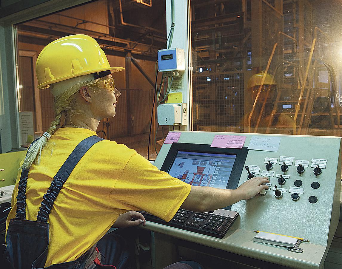 Eine Mitarbeiterin bedient in einer Fabrik eine Maschine per Control-Panel