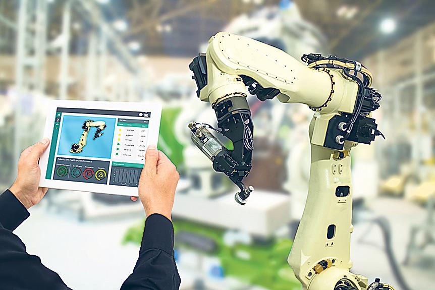 Ein Mann hält ein Touchpad mit dem Abbild eines Roboterarmes neben diesen. Thema: Industrial Internet of Things
