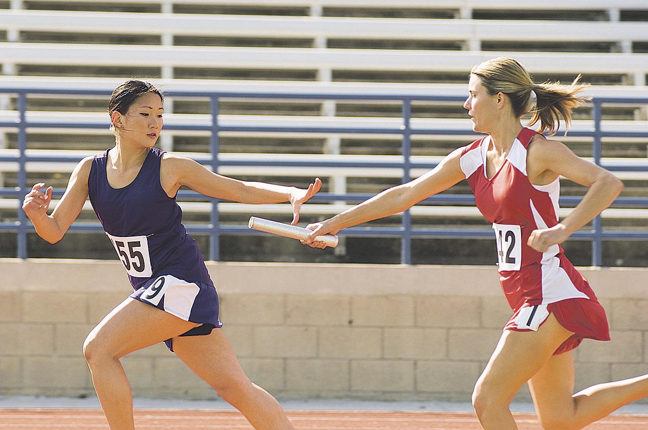 Eine Läuferin übergibt der anderen die Staffel