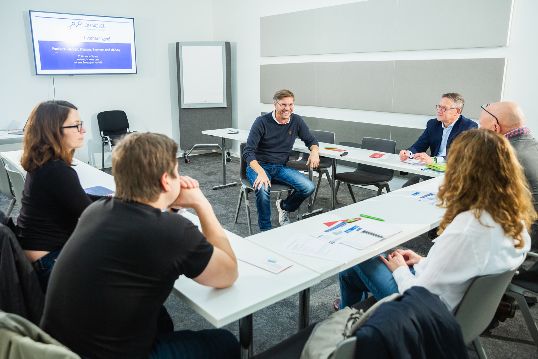 Sechs Personen sitzen in einem Meetingraum und unterhalten sich.