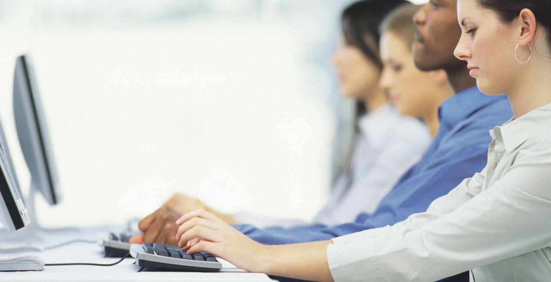 Frauen und Männer an PC-Tastaturen