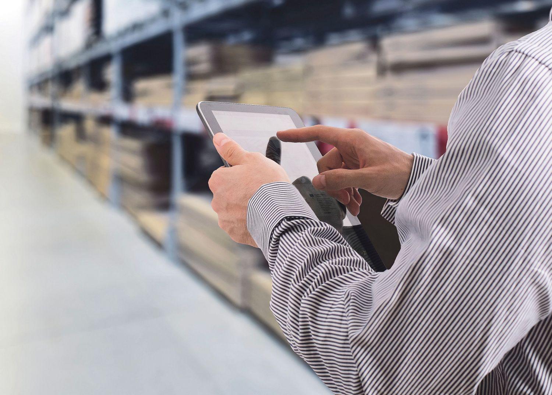 Ein Mann tippt in einem Warenlager etwas in ein Tablet-Display
