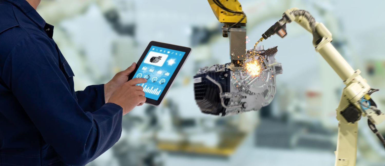 Fabrikarbeiter steuert über ein Tablet mittels eines IoT-Gateways eine Maschine.