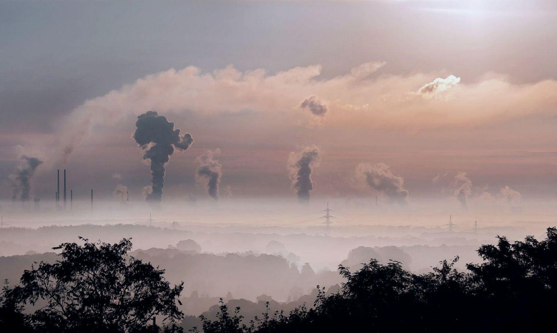 Rauchwolken steigen im Sonnenaufgang aus Schornsteinen am Horizont auf