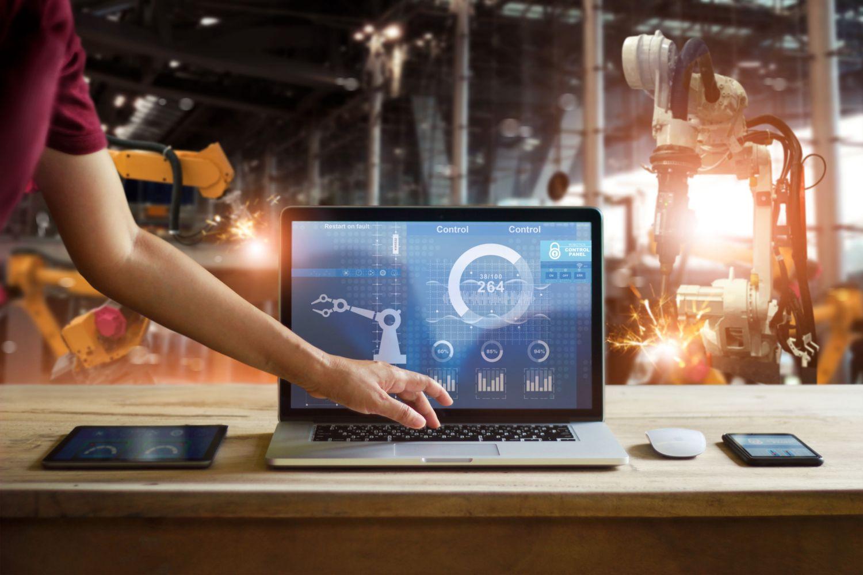 Eine Hand tippt auf einem Laptop, der wiederum Anlagen in einer Produktionshalle steuert. Thema: Modularisierung von Software für Anlagensteuerung