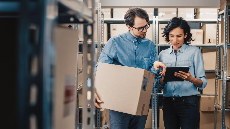 Zwei Lagermitarbeiter schauen auf ein Tablet; Thema: Automatisierung in der Logistik