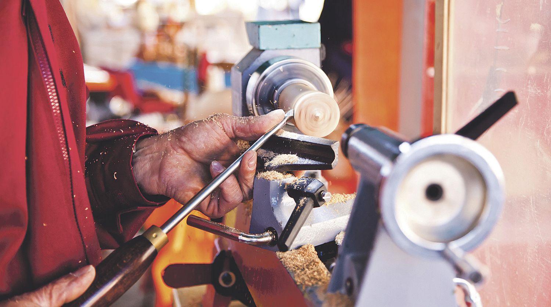 Ein Mensch bearbeitet ein Werkstück an der Drechselbank