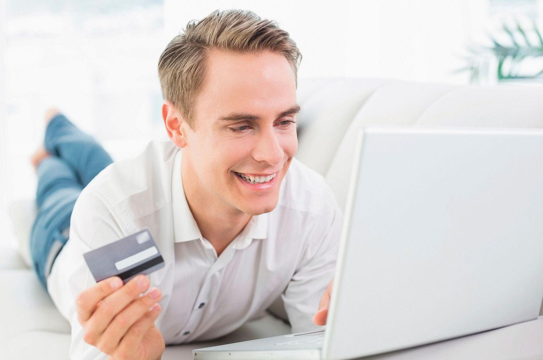 Ein Mann liegt lächelnd vor seinem Laptop, in seiner rechten Hand hält er eine Magnetkarte