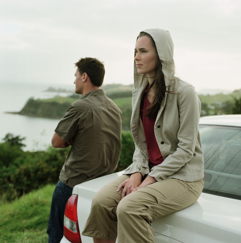 Eine Frau im Kapuzenpulli sitzt auf dem Kofferraum eines Autos und schaut mit einem Mann auf das Meer, der sich an das Auto lehnt. Thema: Tabu Hacker-Angriffe
